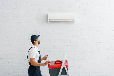 Workman holding screwdriver near toolbox on ladder and looking at air conditioner on wall