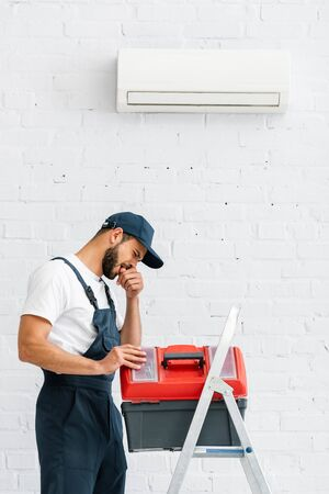 Injured workman with finger near mouth opening toolbox on ladder near air conditioner on wall