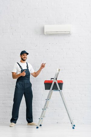 Smiling workman showing thumb up while holding remote controller of air conditioner near toolbox on ladder Stock fotó