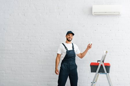 Handsome workman in overalls smiling while holding remote controller of air conditioner beside toolbox and ladder