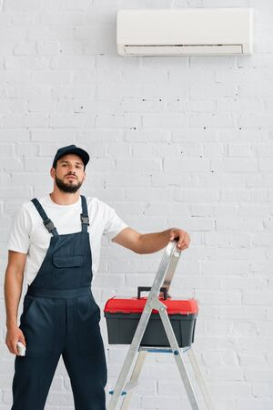 Handsome workman looking at camera while holding remote controller of air conditioner near toolbox on ladder