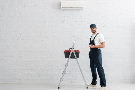 Smiling workman holding remote controller of air conditioner near toolbox on ladder