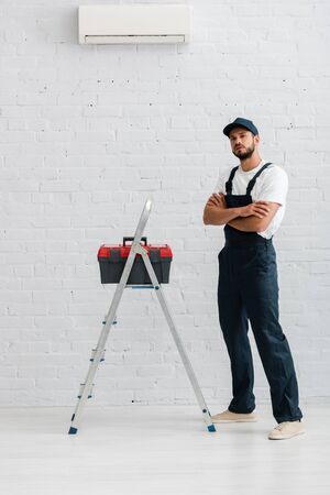Handsome workman in overalls looking at camera near toolbox on ladder and air conditioner on white wall