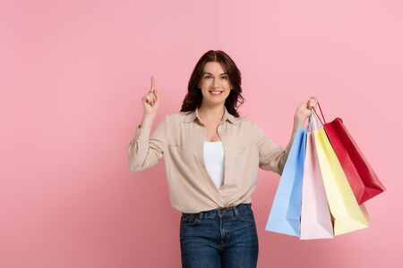 Positive brunette woman pointing with finger while holding shopping bags on pink background 版權商用圖片