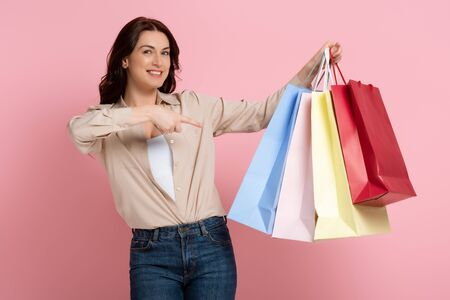 Beautiful brunette woman smiling at camera and pointing with finger at colorful shopping bags on pink background 版權商用圖片