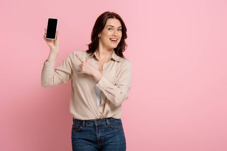 Positive brunette woman pointing with finger at smartphone with blank screen on pink background