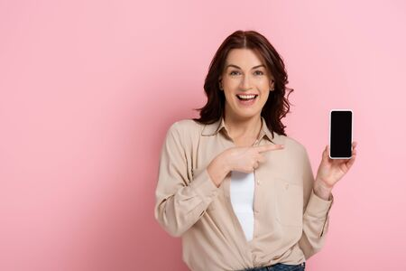 Beautiful woman smiling at camera while pointing with finger at smartphone with blank screen on pink background