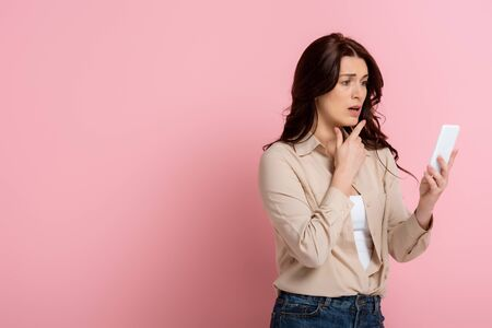 Worried woman pointing with finger while using smartphone on pink background