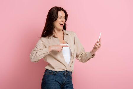 Positive woman pointing with finger at smartphone on pink background 版權商用圖片