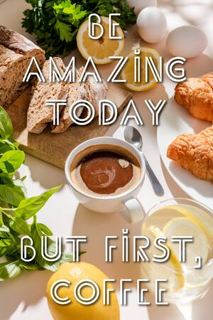fresh croissants, bread, greenery, eggs, lemon water and cup of coffee for breakfast on grey table with be amazing today, but first, coffee lettering