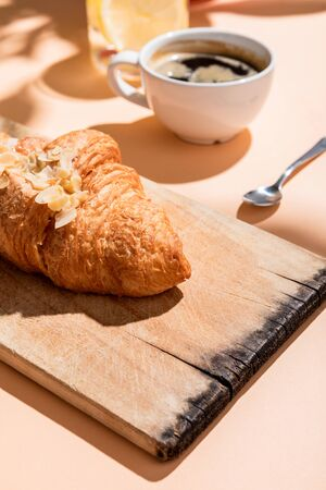 fresh croissants on cutting board and cup of coffee for breakfast on beige table