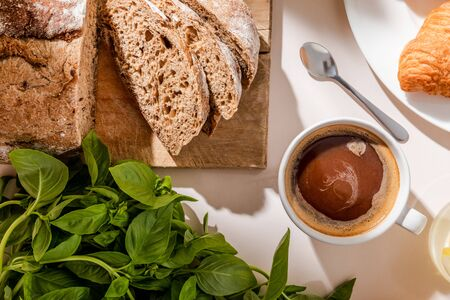 top view of bread, basil and cup of coffee for breakfast on grey table