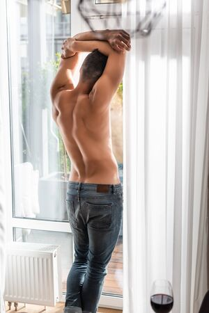 selective focus of muscular man in jeans standing near window Zdjęcie Seryjne