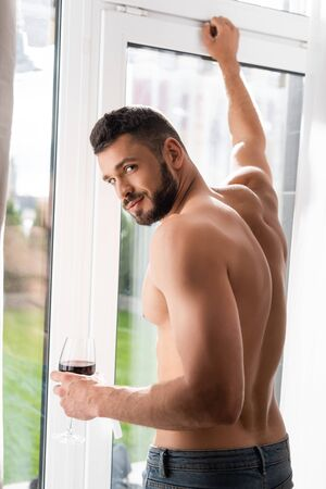 muscular and bearded man holding glass of red wine