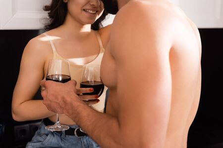 cropped view of shirtless man and smiling girl holding glasses with red wine