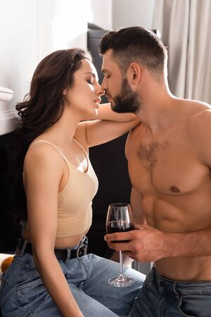 side view of shirtless man holding glass of red wine near attractive girl with closed eyes