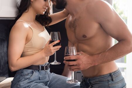 cropped view of muscular man and woman holding glasses of red wine Zdjęcie Seryjne