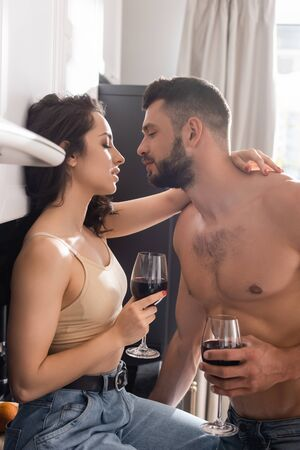 side view of handsome muscular man and beautiful woman holding glasses of red wine Zdjęcie Seryjne