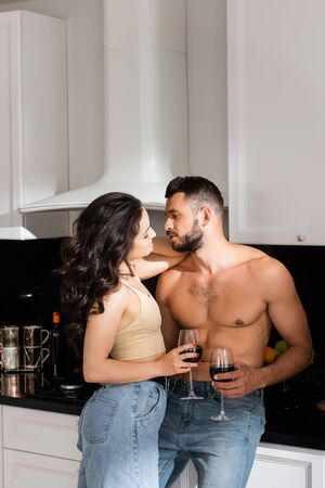 beautiful girl and handsome muscular man looking at each other and holding glasses with red wine Zdjęcie Seryjne