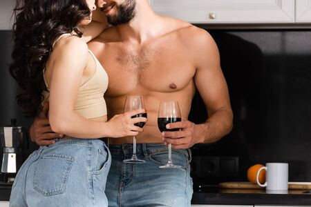 cropped view of happy muscular man and girl holding glasses of red wine
