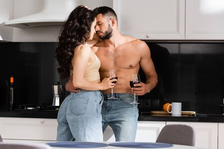 selective focus of young woman holding glass of red wine and looking at shirtless man