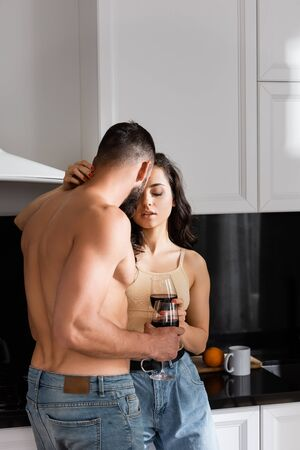 young woman holding glass of red wine and hugging shirtless man Zdjęcie Seryjne