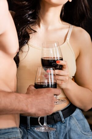 cropped view of shirtless man and young woman holding glasses of red wine Zdjęcie Seryjne