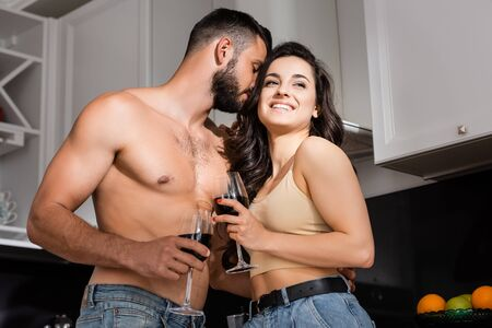 low angle view of shirtless man smelling hair of happy young woman holding glass of red wine