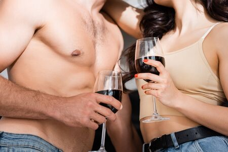 cropped view of muscular man and young woman holding glasses of red wine