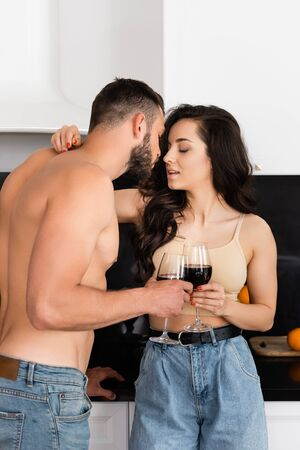 shirtless man and attractive woman with closed eyes holding glasses of red wine