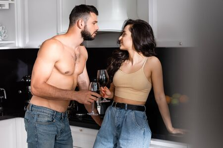 selective focus of shirtless man and happy woman holding glasses of red wine and looking at each other Zdjęcie Seryjne