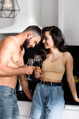 shirtless man and happy woman holding glasses of red wine