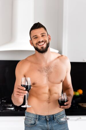 happy and shirtless man holding glasses with red wine