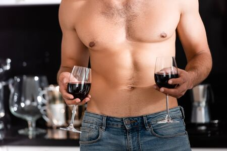 cropped view of muscular man holding glasses with red wine