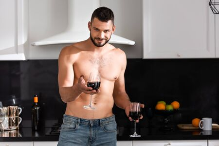 happy and muscular man holding glasses with red wine Zdjęcie Seryjne