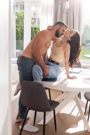 bearded and muscular man hugging sexy girl sitting on table near laptop