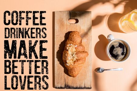 top view of coffee, water and croissant on wooden board for breakfast on beige table with coffee drinkers make better lovers lettering