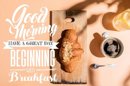 top view of coffee, water and croissant on wooden board on beige table with good morning, have a great day, beginning with breakfast lettering Foto de archivo