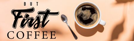 top view of coffee cup and teaspoon on beige with but first coffee lettering, website header Foto de archivo