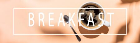 top view of coffee cup and teaspoon on beige with breakfast lettering, horizontal concept