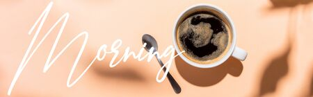 top view of coffee cup and teaspoon on beige with morning lettering, website header Foto de archivo