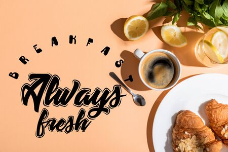 top view of coffee and croissants on beige table with breakfast always fresh lettering Foto de archivo