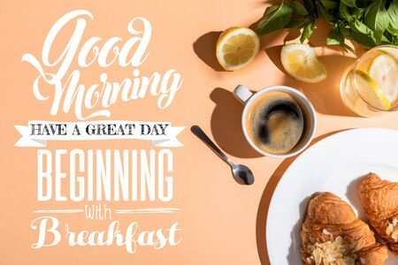 top view of coffee and croissants for breakfast on beige table with good morning, have a great day, beginning with breakfast lettering Foto de archivo