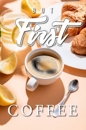 coffee cup with teaspoon, croissants and glass of water with lemon for breakfast on beige table with but first coffee lettering Archivio Fotografico