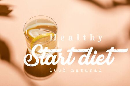 glass of fresh water with lemon slices on beige with healthy start diet 100 percents natural lettering