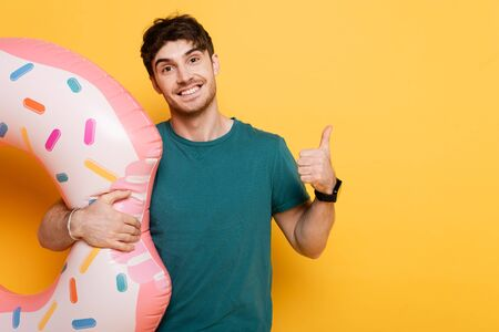 smiling man showing thumb up while standing with inflatable donut on yellow
