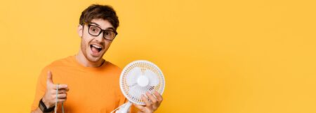 excited man in eyeglasses holding shopping bag with new electric fan on yellow, website header