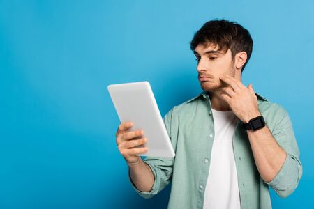 thoughtful young man touching face while looking at digital tablet on blue