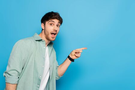 shocked young man looking at camera and pointing with finger on blue