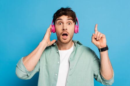 shocked young man touching wireless headphones and showing idea gesture on blue